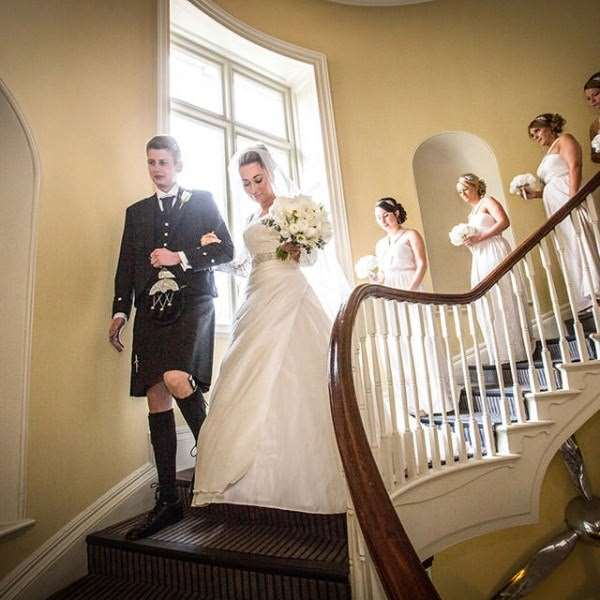 Bride and bridesmaids walking down a stairwell at Kesgrave Hall